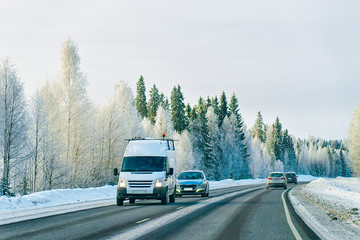 Minivan and cars in road in winter Rovaniemi