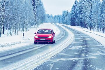 Red Car in road in winter Rovaniemi