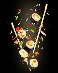 Pieces of sushi frozen in the air on black background