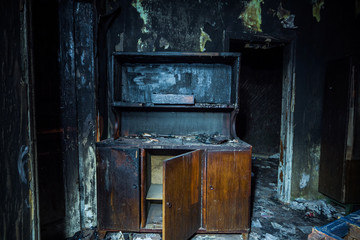 Consequences of fire. Interior of the burned by fire house, burned furniture