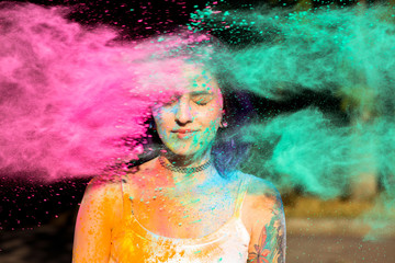 Beautiful brunette woman posing with exploding pink and green Holi powder around her