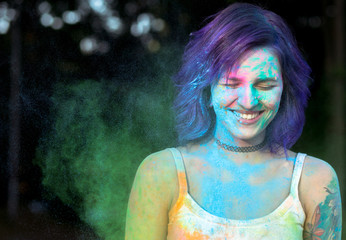 Positive woman with purple hair having fun with dry Holi powder. Space for text