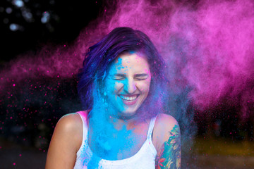 Laughing young woman with dry powder Holi exploding around her