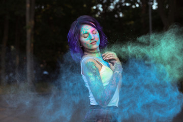 Romantic woman with purple hair posing with exploding Holi powder at the park