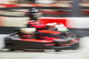 Fotomurales - Cart blurred by high speed, a boy having fun - driving fast, racing, speeding.