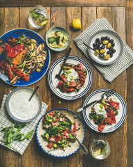 Flat-lay of healthy dinner table setting. Fresh salad, grilled vegetables with yogurt sauce, pickled olives, lemon water over wooden background, top view, square crop. Clean eating, vegetarian food