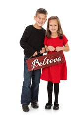 Christmas: Brother And Sister Hold Believe Sign