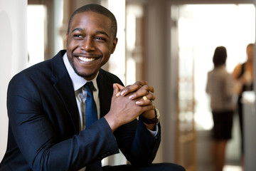 Enthusiastic chic handsome charismatic classy african american CEO in his office smiling confidently