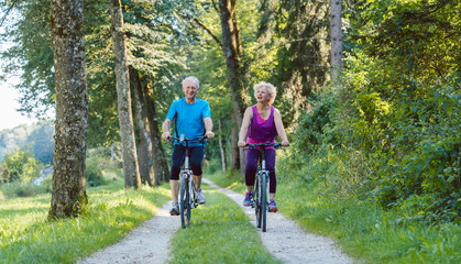 Full length of a happy and active senior couple wearing cool fitness outfits while riding bicycles outdoors in the park