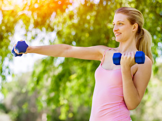 Portrait of cheerful woman in fitness wear exercising with dumbbell