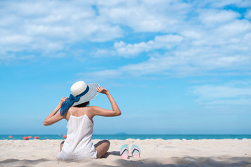 Woman in sun hat relaxing at sunny beach Tropical and remote beaches
