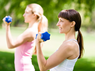 Portrait of cheerful women in fitness wear exercising with dumbbell