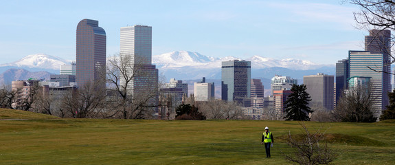 A worker walks down a fairway at the City Park golf course with the downtown city skyline in the background in Denver
