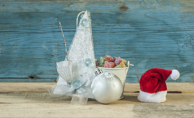 Handmade christmas decoration and colorful candy on wooden background.
