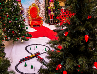 A Christmas setting with a toy train, christmas trees, and Santa's helpers.