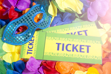 Brazil tickets sit with a sparkly carnival mask on a background bed of colorful flower leis with party lens flare lighting
