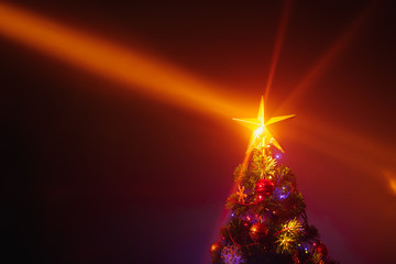 Christmas tree with festive lights, orange background with mist