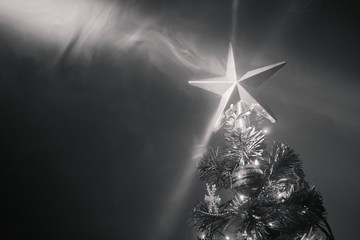 Christmas tree with festive star in smoke, black and white