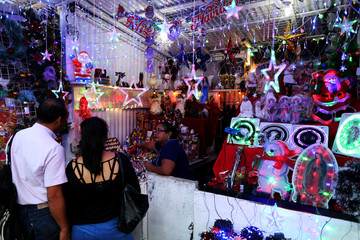 People buy decorations at the Christmas market at the Simon Bolivar park in San Salvador