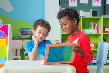 Two boy kid sit on table and reading tale book  in preschool library,Kindergarten school education concept