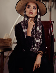 Model with a big scarf and hat sitting on a chair in a Mexican style in studio