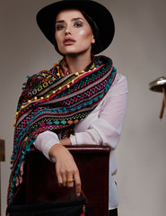 Model with a colourful scarf and big hat sitting on a flipped chair in a Mexican style in studio