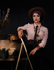 Model sitting on a ladder in a tie and Mexican style in studio