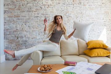 cheerful beautiful girl jumps on a sofa. Freelancer, computer.