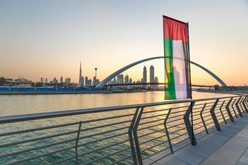Dubai Downtown skyline with UAE national flag at sunrise. Dubai, UAE.