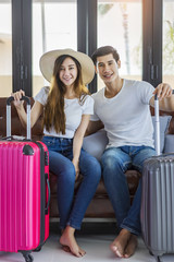 Happiness Asian couple traveler packing suitcases preparing for travel vacation together.Happy enjoy to smiling at home in the living room.