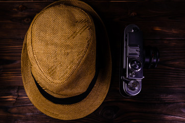 Old rangefinder camera and hat on a wooden table