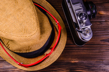 Old rangefinder camera, sunglasses and hat on a wooden table. Top view