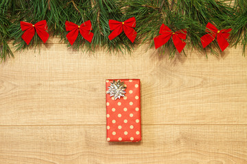 New Year / Christmas gift in package, tree with red bows on the wooden background template