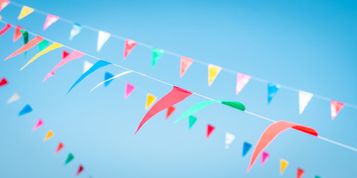 Fair flag blur bunting background hanging on blue sky for fun festa event, summer holiday farm feast, carnival festival event, park or street design decoration element