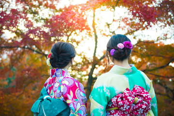 Two Japanese women in Kimono dressing is smiling and enjoy sightseeing maple trees during autumn inside Nara park in Nara-shi, Japan.