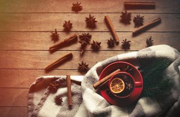 Cup of tea with lemon and scarf near cinnamon nad star anise