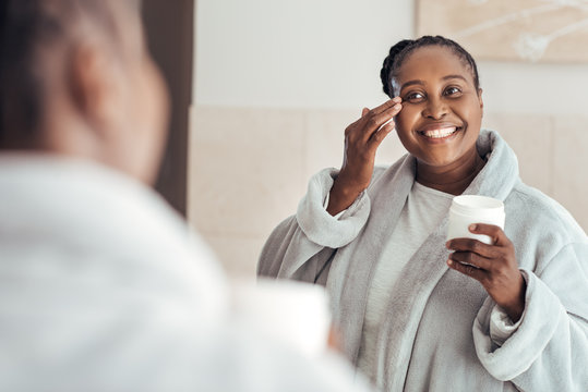Smiling young African woman putting on face cream at home