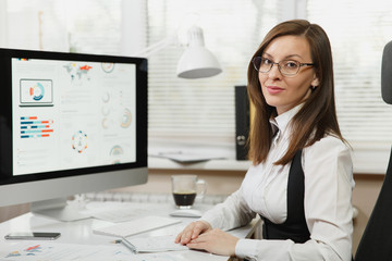 Beautiful smiling brown-hair business woman in suit and glasses sitting at the desk with cup of coffee, working at computer with documents in light office, looking at the camera