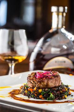 Beef Steak. Grill beef steak black lentils mixed with vegetable. Cognac or brandy as drink. Culinary food in hotel pub or restaurant