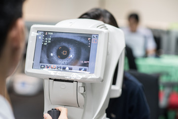 Woman looking at refractometer eye test machine in ophthalmology