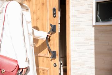 玄関ドアを開ける女性