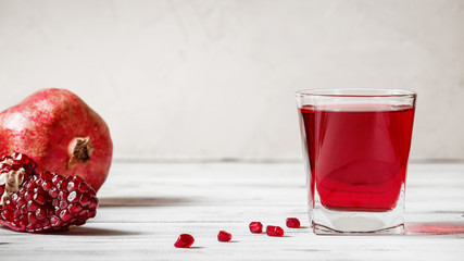 Glass of pomegranate juice with fresh pomegranate fruit