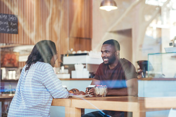 Young African couple talking together over coffee in a cafe