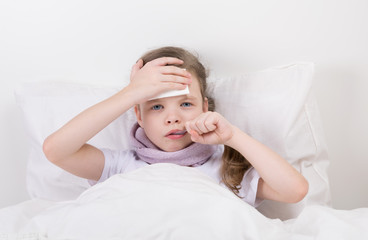 girl in bed with a headache, taking medicine