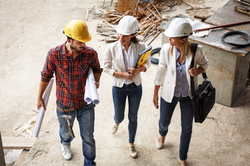 Two female inspectors and architects walk with head engineer trough construction site.