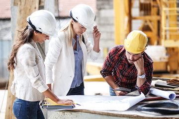 Two female inspectors and architects discuss with head engineer about construction project.People at work concept.