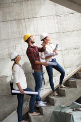 Two female inspectors and architects walking and discuss with head engineer on construction site.They examining the stair way.