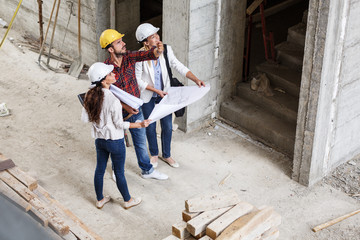 Two female  architects discuss with head engineer about building project.
