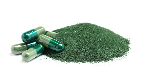 Pile of spirulina powder and capsules on white background