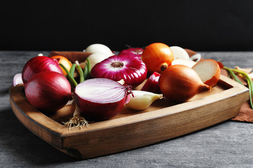 Different fresh onions on wooden board
